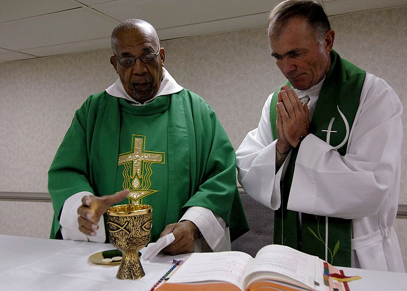 Father Joseph Harris, left, a Roman Catholic priest in Trinidad and Tobago, celebrates mass with Lt. Cmdr. Paul Evers