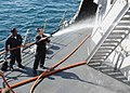 US Navy 100220-N-7088A-088 Damage Control Fireman Erin Lagos sprays down part of the Arleigh Burke-class guided-missile destroyer USS Farragut (DDG 99).jpg