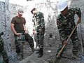 US Navy 100806-N-3317W-025 Utilitiesmen 2nd Class Erik Dines, assigned to Naval Mobile Construction Battalion (NMCB) 11, instructs Timorese Defense Force F-FDTL workers how to properly use a jack hammer.jpg