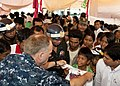 US Navy 101028-N-6770T-055 Lt. Cmdr. Mike Morley, assigned to Commander Task Force 73 in Singapore, hands out donated clothes to local children at.jpg