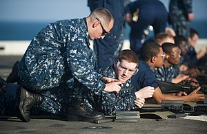 US Navy 111210-N-PB383-563 Chief Gunner's Mate Frank Smith instructs Logistics Specialist 2nd Class David Elliot during small arms qualifications a.jpg