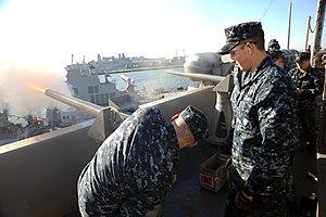 US Navy 111219-N-AU622-059 Airman Apprentice Cody Lichvar observes as Gunner's Mate 3rd Class Phillip Furlong fires a 17-gun salute for Admiral Joh.jpg
