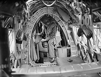 "Aircraft lavatory - A crewman on board a World War 2 Royal Air Force Vickers Wellington bomber. The container to the right of him is the aircraft's ""Elsan"" chemical toilet (1939-1941)"