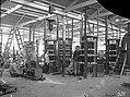 Vijf transformatorzuilen in opbouw. Op de voorgrond een luchtcompressor, gedreven door een elektromotor.jpg