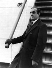 A half-length portrait of Vladimir Horowitz stood by the steps of a boat, facing left. The photo was taken in 1931, when Vladimir Horowitz was in his late twenties. He is wearing a long coat, leather gloves, a white shirt and a tie.