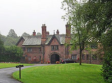 A two-storey house including an archway under a gable and another gable with half-timbering. In front of it is an area of grass and trees.