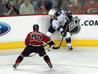 National Hockey League - Los Angeles Kings' Mike Weaver clearing the puck away from Calgary Flames' Daymond Langkow, December 21, 2005.