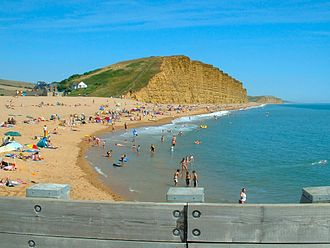 West Bay, Dorset - East Beach and East Cliff. Before the mid 18th century, the harbour and river mouth were near the base of the grassy slope