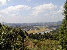 Photographie d'un paysage dans le nord du bassin du Sichuan. Le premier plan fait place à une forêt, puis vient une large plaine dans laquelle coule un cours d'eau.