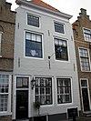 foto van Huis met geverfde lijstgevel, aan de hoeken ingezwenkt. Kalf en tandlijst. Stoeptreden