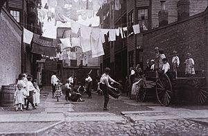 Photo en noir et blanc montrant des enfants jouant au baseball, des enfants assis sur une charrette les regardent