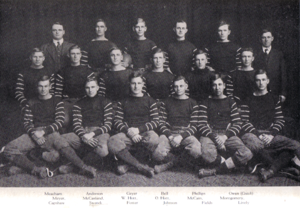 Sixteen young men in American football uniform, and two older men in jackets, sitting in three rows.