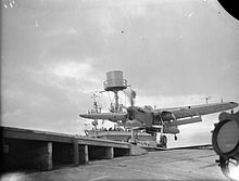 Black-and-white photograph of a single-engined monoplane running along the deck of an aircraft carrier