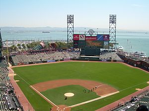 View of a baseball stadium, taken from the upper deck and looking out over the field from behind the backstop. The field, bleachers, scoreboard and advertisements are all visible, with a backdrop of a bay of water and distant hillside.