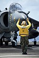 A flight deck crewman directs the pilot of an AV-8B Harrier jet aircraft during flight operations aboard the amphibious assault ship USS Bonhomme Richard (LHD 6) in the Philippine Sea 120915-N-KB563-163.jpg