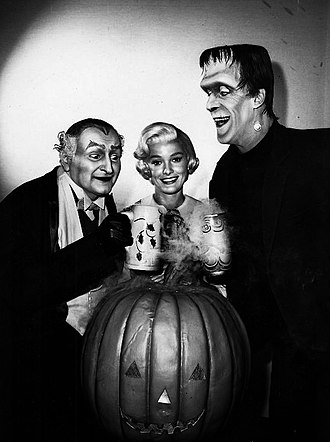Fred Gwynne - Gwynne as Herman, sharing a toast with Al Lewis (Grandpa) while Beverley Owen (Marilyn) looks on