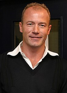 Alan Shearer wearing a black jumper with a white collar visible