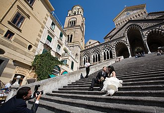 Christian views on marriage - A couple posing for wedding photos on the steps of a church in Italy