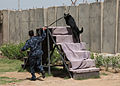 An Iraqi Police K9 dog runs an obstacle course, assisted by his trainer in Basrah, Iraq, May 3, 2011 110503-A-YD132-141.jpg