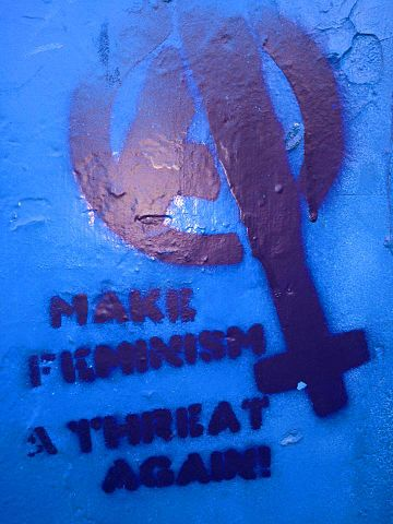 "Stencil graffiti on a blue background, a woman's symbol with an A inside, next to the words ""Make feminism a threat again"""