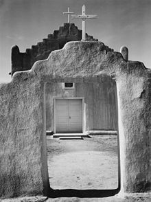 A black-and-white vertical photograph shows an adobe wall in the foreground, rising in the middle with a stairstep pattern and a white wooden cross at the pinnacle, with an open doorway beneath. Through the doorway and above the wall, an adobe church with white double doors and a similar stair-stepped roof and cross stands, slightly larger than the wall in front of it. The midday sun casts harsh shadows on the dirt ground.