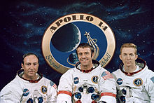 Mitchall, a smiling Shepard and Roosa wearing their Apollo space suits without the helmets. Their suits sport their names, the mission patch on the left breast and NASA patch on the right. The wear the American flag on their left sleeve. Shepard has red rings in his arms. In the background is a giant mission patch, surrounded by black space and stars.