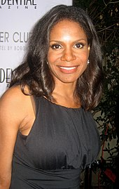 Audra McDonald in a black dress against a white background