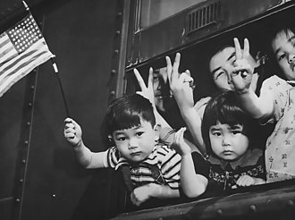 Bainbridge Island, Washington - A group of Japanese-American residents of Bainbridge Island wave the American flag and give the victory sign as they are forcibly evacuated to an internment camp, March 30, 1942.