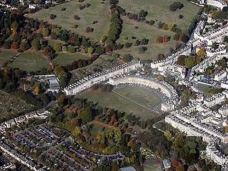 "Bath, Somerset - Royal Crescent and Circus from the air (connected by link road, thus creating the famous ""question mark"" formation). Georgian taste favoured the regularity of Bath's streets and squares and the contrast with adjacent rural nature."