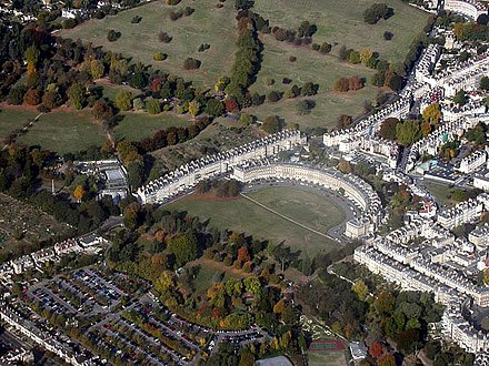 "Royal Crescent and Circus from the air (connected by link road, thus creating the famous ""question mark"" formation). Georgian taste favoured the regularity of Bath's streets and squares and the contrast with adjacent rural nature. BathRoyalCrescentAirial morecontrast.jpg"