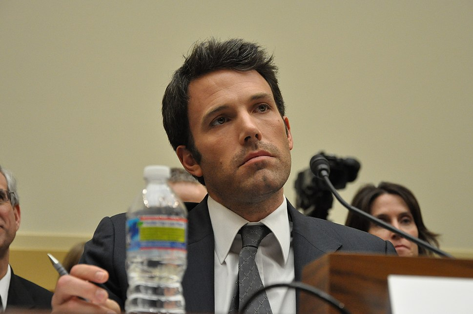 Ben Affleck, holding a pen and sitting behind a microphone, looks ahead while offering testimony