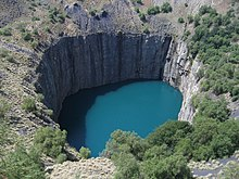 helikoptervy av en cirkulär utgrävning huggen i berget, fylld med vatten