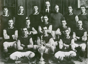 Fourteen footballers pose for a team photograph with a silver trophy in front of them. The team manager stands behind the players.