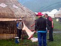 Butchering a sheep to feed visitors from bus tour in July 2012 in Altay prefecture of northwest China.jpg