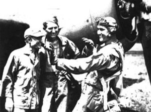 Harold W. Bauer - Bauer, at right, explains his technique to two ground crewmen.