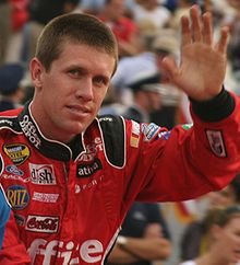 Edwards, with close cropped hair, waves while wearing his red, sponsor filled racing suit