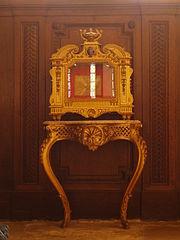 Reliquaire doré doté d'une vitre et posé sur une console de bois doré.