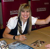 Catherine Hardwicke smiling while signing some DVDs.