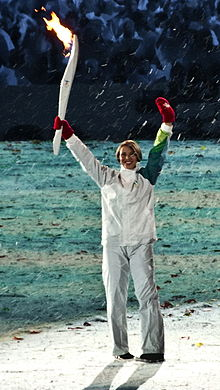 Catriona Le May Doan standing, holding a lit torch in her right hand, waiving to the crowd at the 2010 Winter Olympics opening ceremony.