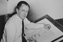 Black-and-white photograph of a man seated at a drawing table and drawing a cartoon