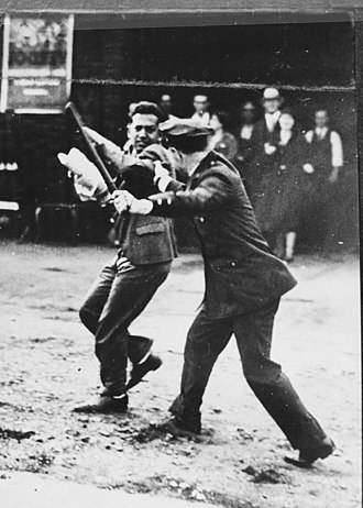 1934 West Coast waterfront strike - Image: Confrontation between a policeman wielding a night stick and a striker during the San Francisco General Strike, 1934 NARA 541926