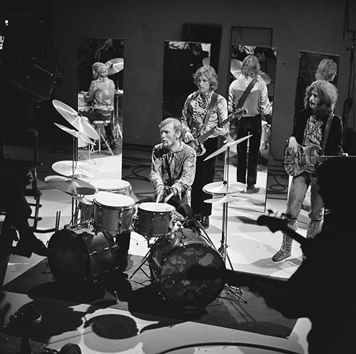 The band Cream is shown playing on a TV show. From left to right are drummer Ginger Baker (sitting behind a drumkit with two bass drums) and two electric guitarists.