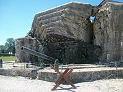A heavily damaged concrete fortification with a protruding gun barrel.