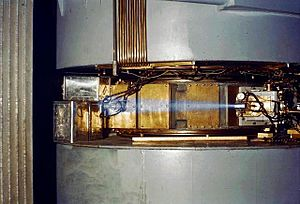 """60-inch cyclotron, circa 1939, showing a beam of accelerated ions (likely protons or deuterons) escaping the accelerator and ionizing the surrounding air causing a blue glow. This phenomenon of air ionization is analogous to the one responsible for producing the """"blue flash"""" infamously noted by witnesses of criticality accidents. Though the effect is often mistaken for Cherenkov radiation, this is not the case."""