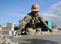 Defense.gov News Photo 110111-N-2984R-363 - U.S. Navy Petty Officer 2nd Class Andras Toth assigned to Naval Mobile Construction Battalion 28 trowels the foundation of a new classroom being.jpg