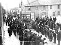 Dogsled team on crowd-lined street near the Hotel Sheldon and the Lomen Brothers photography studio in Nome, April 11, 1916 (AL+CA 6277).jpg