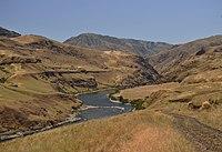 Narrow river turning between brown hills