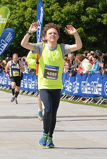 A Runner Crosses The Finish Line At Edinburgh Marathon
