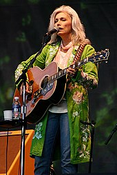 A woman with long grey hair wearing a long green jacket, playing a guitar and singing into a microphone