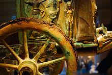 Photographie montrant une roue à rayons en bronze oxydé et en arrière plan le corps même du char avec des bas-reliefs.